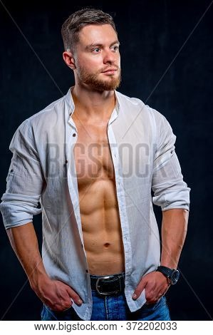 Super Sexy Man With Tan Abs And Chest. Athletic Man With Unbuttoned White Shirt On Dark Background.