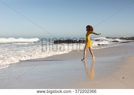 A happy, attractive mixed race woman with her arms outstretched enjoying free time on beach on a sunny day, wearing a yellow dress, walking with sun shining on her face.