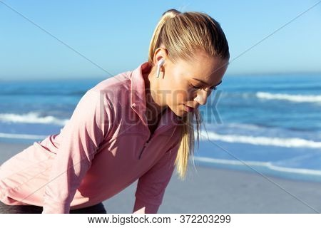 Close up of a Caucasian woman wearing sports clothes, enjoying time at the beach on a sunny day, taking a break, wearing earphones