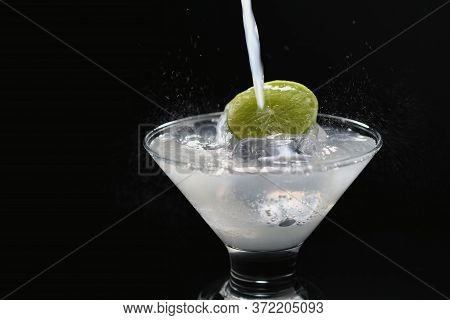 Close-up Of Cocktail With Ice And Lime On Black Background