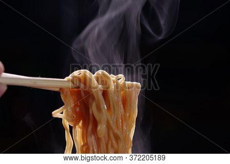 Chopsticks To Tasty Noodles On Dark Background