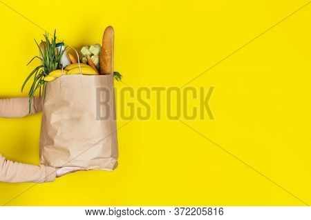Food Delivery Or Donation Concept. Grocery Store Shopping. Girl Or Woman Holds A Paper Bag Filled Wi