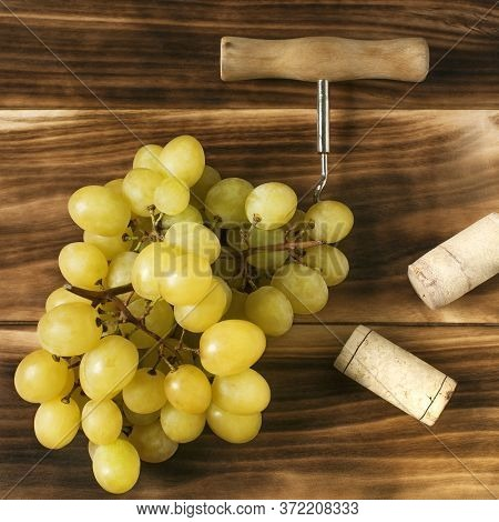 Wine Cork, Corkscrew And A Grape Branch On A Wooden Background, Still Life For Restaurants