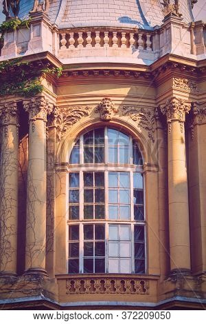 Arched Window With A Beautiful Ancient Stone Relief Ornamental Decoration, Portrait, Floral Elements