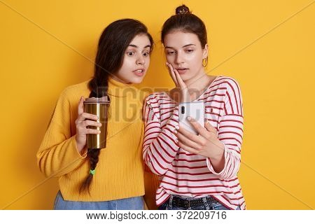 Ladies With Smart Phone In Hands And Take Away Coffee, Women Looking At Device Screen With Shocked F