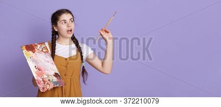Young Caucasian Woman Artist With Two Pigtails Holding Paint Brush And Palette In Hands. Female Pain