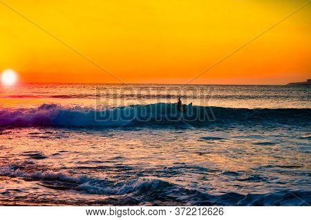 The Silhouette Of A Surfer Riding A Wave At An Empty Surf Spot. Young Surfer Rides The Wave During S