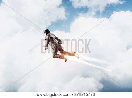Businessman In Suit And Aviator Hat Flying In Blue Sky As Superhero. Corporate Manager As Superman L