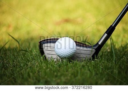 Golf Club And Golf Ball Close Up In Grass Field With Sunset. Golf Ball Close Up In Golf Coures At Th