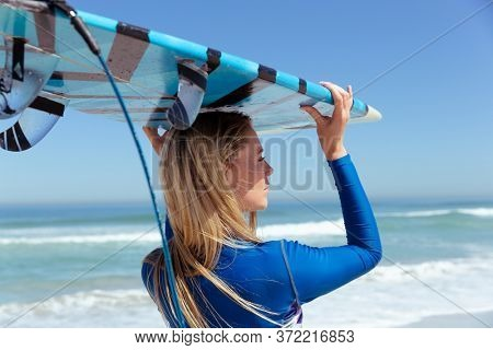 A Caucasian woman enjoying time at the beach on a sunny day, holding surfboard and walking, with sea in the background