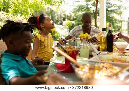 A multi-ethnic, multi-generation family sitting down at a table holding hands with eyes closed and saying a prayer before having a meal outside on a patio in the sun.