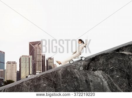 Beautiful Happy Woman Riding Downhill On Mountain Road. Young Employee In White Business Suit Going