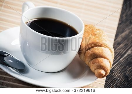 Cup Of Espresso Coffee On Wooden Table. Traditional French Breakfast. White Porcelain Cup And Delici