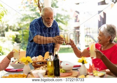 A mixed race senior man raising a glass of lemonade and making a toast with his multi-ethnic adult family, sitting at the table and raising their glasses during a meal together outside on a patio