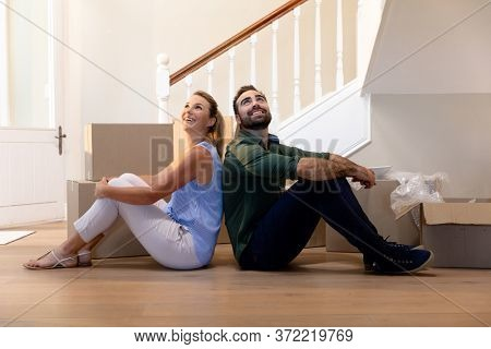 Caucasian couple sitting back to back on the floor in the hallway of their new home, taking a break from moving in and looking around smiling, cardboard packing boxes on the floor beside them