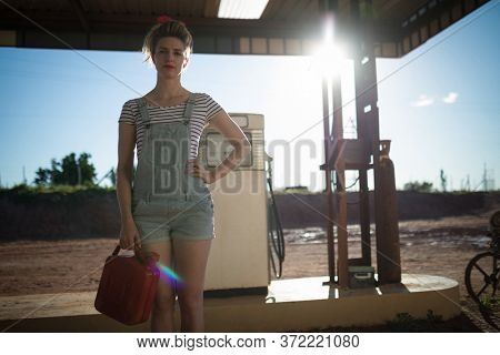 Young woman holding a petrol can at petrol pump