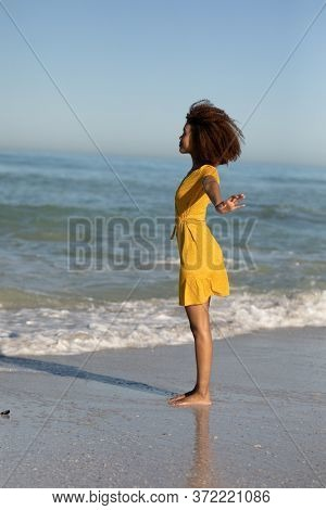 A rear view of a happy, attractive mixed race woman with her arms outstretched enjoying free time on beach, wearing a dress, facing the sea, sun shining on behind her.  Relaxing summer vacation.