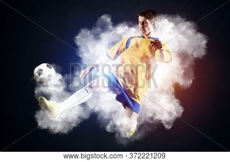Soccer Player Kicking Ball In White Smoke. Sportsman In Yellow And Blue Uniform In Action. Soccer Ga
