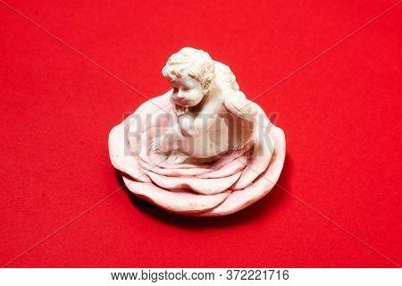 Gypsum Angel Figurine On A Red Background.