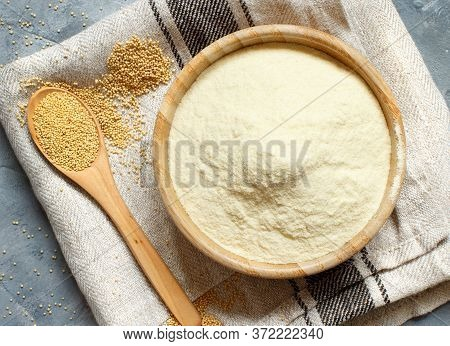 Bowl Of Raw Amaranth Flour With A Spoon Of Amaranth Seeds On A Napkin Top View