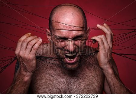 Photo Of Mad Bald Man In Black Threads On Red Background