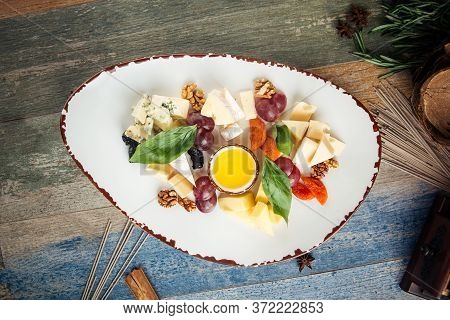 Top View On Classic Wine Appetizer Cheese Grapes Nuts On The Wooden Table, Horizontal