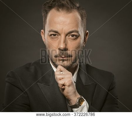 Confident Caucasian Businessman In Formalwear. Boss Stares Forward And Touches Beard With Hand. Clos