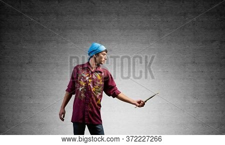 Young Artist Gesturing With Paintbrush. Male Painter In Dirty Shirt And Bandana Standing On Grey Wal