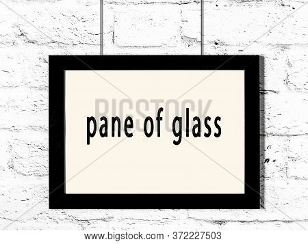 Black Wooden Frame With Inscription Pane Of Glass Hanging On White Brick Wall