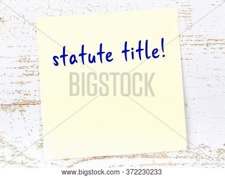 Concept Of Reminder About Statute Title. Yellow Sticky Sheet Of Paper On Wooden Wall With Inscriptio