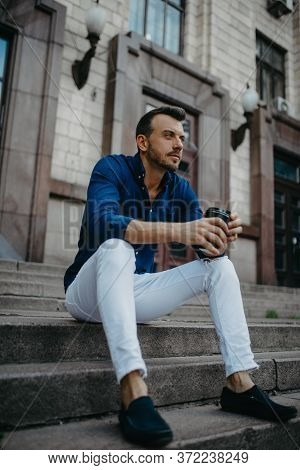 Young Man Sits And Ponders On Stairs With Cup Of Coffee In His Hands Against Background Of Modern Bu