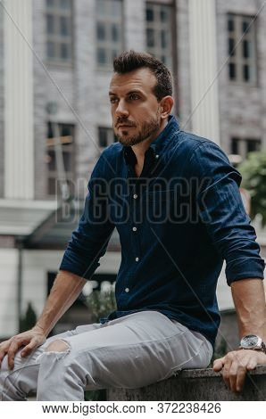 Young Man Sits And Ponders On Bench Against Background Of Modern Building.