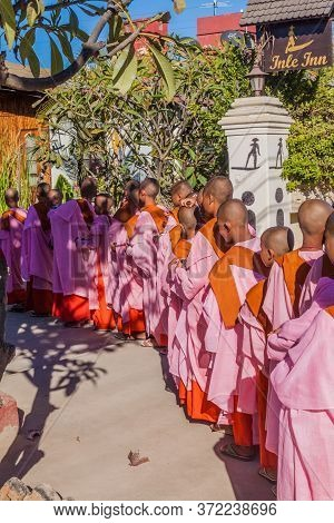 Nyaungshwe, Myanmar - November 27, 2016: Young Buddhist Nuns Wait For Receiving Morning Alms On A St