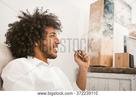 Shaggy Man Rests Smoking E-cigarette. Smiling Sun-tanned Guy Admires Looking At Smoke Clouds. Altern