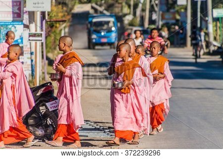 Nyaungshwe, Myanmar - November 27, 2016: Young Buddhist Nuns Go For Morning Alms On A Street In Nyau