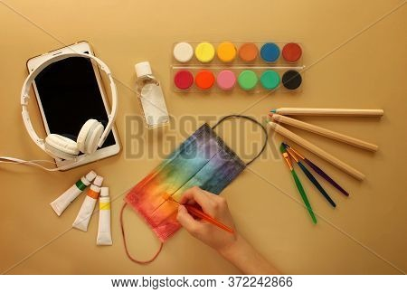 A Child's Hand Paints A Protective Mask In Rainbow Colors Next To School Stationery, Antiseptic, Ele