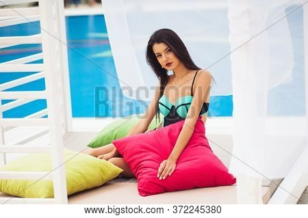 Beautiful Women Relaxing At The Luxury Poolside. Girl At Travel Spa Resort Pool. Summer Luxury Vacat