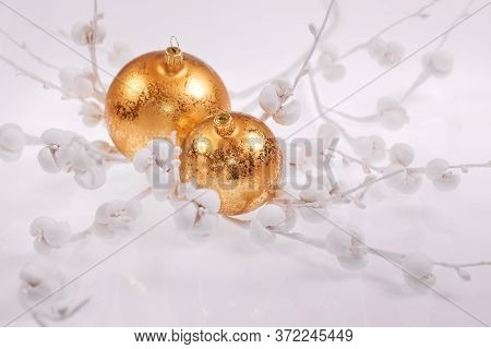 Christmas Decorations On Light Neutral Background. Close-up On Shiny Golden Baubles, Trinkets, On Ne