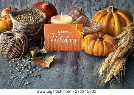 Autumn Harvest Still Life With Pumpkins, Wheat Ears And Lentils In Sackcloth Sack With Cord, Candle