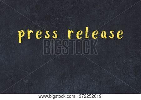 Chalk Handwritten Inscription Press Release On Black Desk