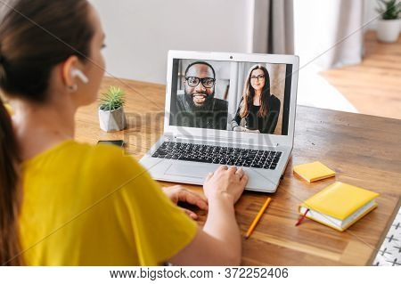 Video Call Of Multiracial Team. A Young Woman Is Talking Online With Coworkers, Friends