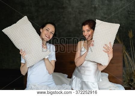 Two Pretty Girls On The Bed In Pajamas. They Have White Pillows In Their Hands. Weekend Fun For Girl