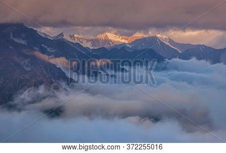 Picturesque Mountain Landscape Shrouded In Fog At Sunset. Caucasus, Russia.