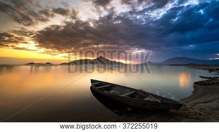 Picturesque Sunset And Boat On The Lake Shore.