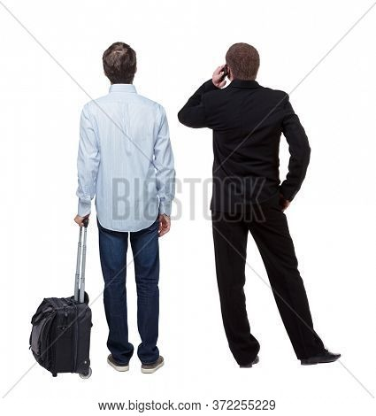Back view of  two business men in suit pointing. Business team. traveling with suitcas. Rear view people collection. backside view of person. Isolated over white background.