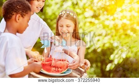 Three children share a watermelon at the children's birthday party in the garden