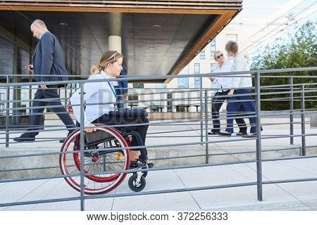 Disabled woman in a wheelchair on her way to work on a ramp to the office