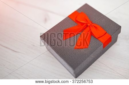Gift Box Present Isolated With Clipping Path With Red Bow Satin On Pine Wood Background.