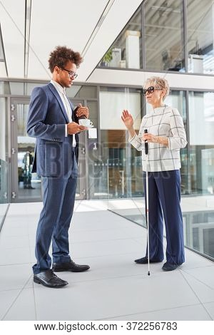 Blind woman with a cane during small talk in the office with an African businessman