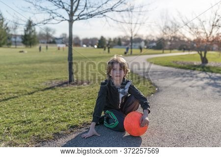 Portrait Of A Child Sitting On The Ground And Holding A Bright Orange Soccer Ball